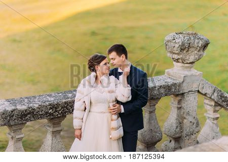 Sensitive portrait of the newlyweds standing near the antique fence at the green background