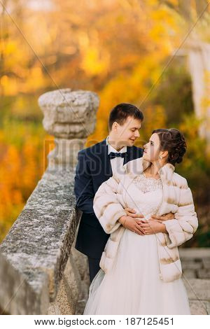 The autunm photo of the groom hugging the bride back while standing on the gothic stairs at the background of the yellowed trees