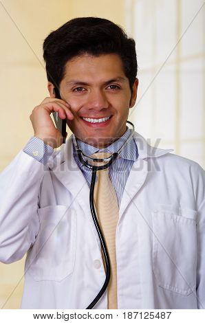 Handsome smiling doctor with an Stethoscope holding from his neck, using his celphone in office background.