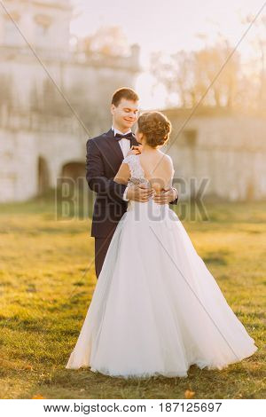 The emotional outdoor photo of the hugging newlyweds during the sunset. The back view of the bride with the bare shoulders