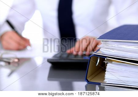 Binders with papers are waiting to be processed with business woman back in blur. Accounting planning budget, audit and insurance concept.