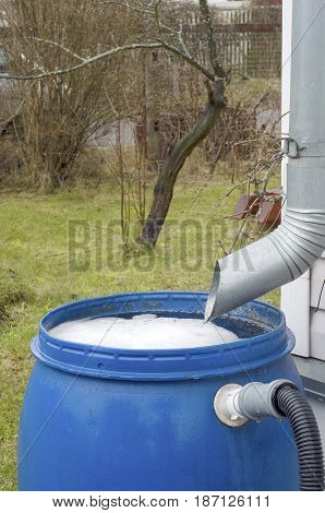 of a metal tube for draining the water flows rainwater in a plastic barrel and blue foams in a country house