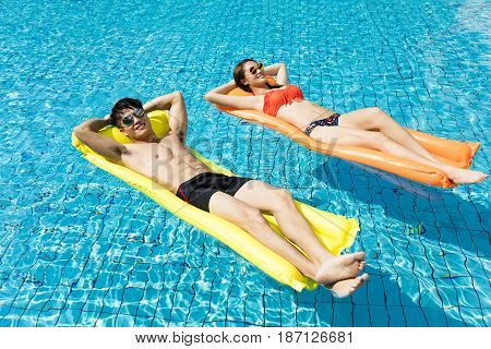 young couple relaxing on inflatable raft at swimming pool