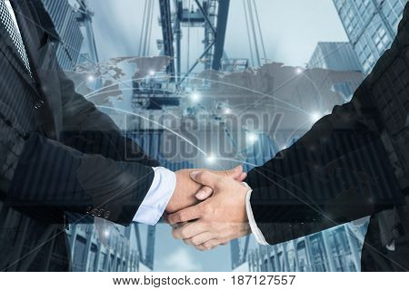 Double Exposure of a businessman handshake with Map global partner connection of Container Cargo freight ship for Logistic Import Export background (Elements of this image furnished by NASA)
