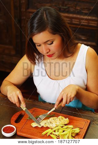 Beautiful girl eating a delicious grilled chicken breast with a small piece of romero spice on wooden board.