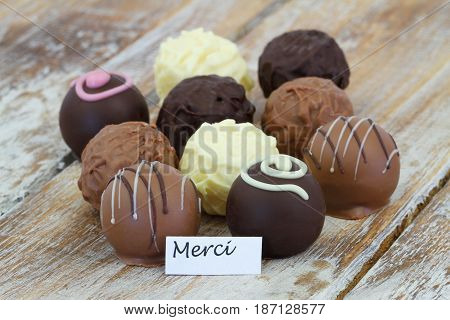 Merci (which means thank you in French) card with assorted chocolates on rustic wooden surface