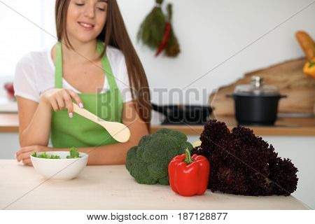Young woman is cooking healthy meal from vegetables at the kitchen. Close up of housewife with wooden spoon pointing into salad and brocolli. Vegetarian concept.