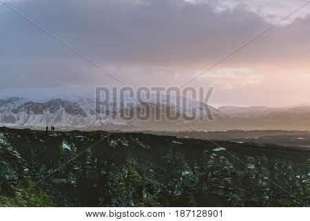 Hiking erupted volcano Kerid In South Iceland with a beautiful sunset and snowy mountains in the background
