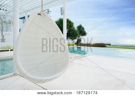 Relaxing white rattan hanging chair at swimming pool on sea view for vacation summer and travel concept.
