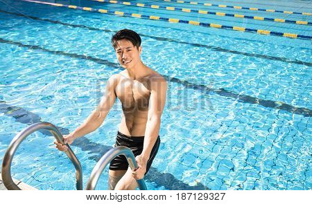 handsome smiling young man in swimming pool
