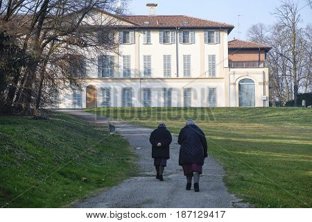 USMATE ITALY - FEBRUARY 18 2017: Two old women walking in the park of the historic Villa Scaccabarozzi in Usmate (Monza Brianza Lombardy Italy)