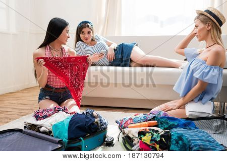 Young Women Packing Suitcases For Vacation Together At Home, Packing Luggage Concept