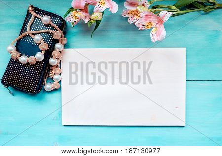 Spring background of bonded wooden boards layout on a blue wooden background with flowers blackboard purse and beads accessories