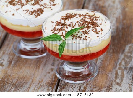 Traditional strawberry trifle dessert with fresh whipped cream and sprinkled with chocolate on rustic wood