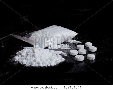 Cocaine drug powder bag and pile and pills on black background