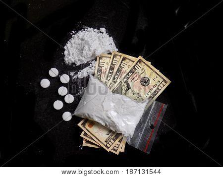 Cocaine drug powder bag, pile and line, pills and dollar money bills on black background