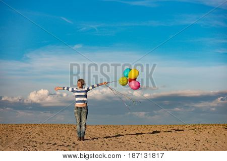 Birthday girl with open arms outdoor with toy balloons