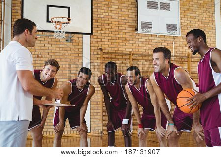 Smiling coach explaining game plan to basketball players in the court