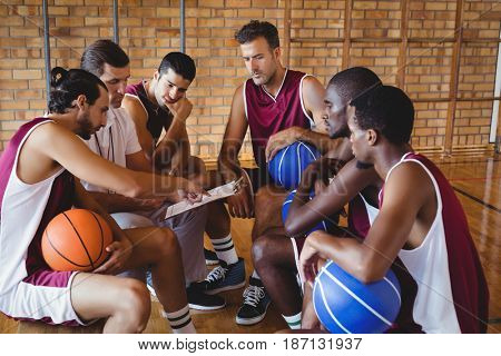 Coach explaining game plan to basketball players in the court