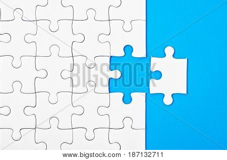 Missing jigsaw puzzle pieces on blue background