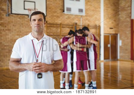 Portrait of confident coach standing in basketball court