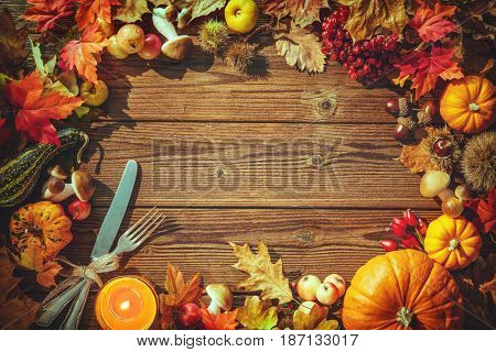 Autumn background from fallen leaves, fruits with vintage place setting and burning candle on old wooden table. Thanksgiving day concept
