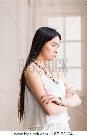 Portrait Of Beautiful Asian Woman In White Dress With Arms Crossed