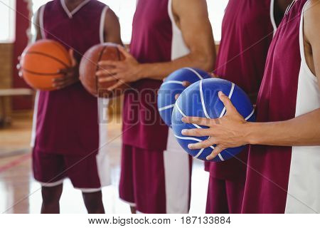 Mid section of basketball players holding basketball in court