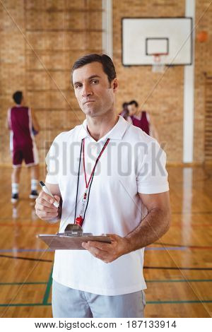 Portrait of basketball coach holding clipboard in the court