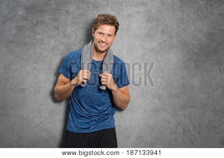 Happy young man standing after workout and leaning on grey background. Smiling guy holding towel on shoulder feeling fresh after fitness training. Satisfied guy looking at camera.