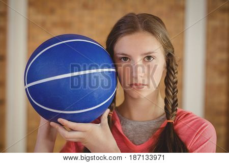 Portrait of determined girl holding a basketball in the court