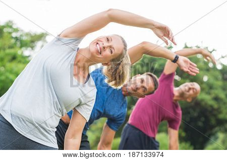 Group of mature healthy people doing stretching at park. Fitness middle aged group exercising outdoor. Three happy people in a row doing stretching arm and smiling.