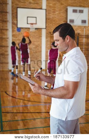 Basketball coach writing on clipboard in the court