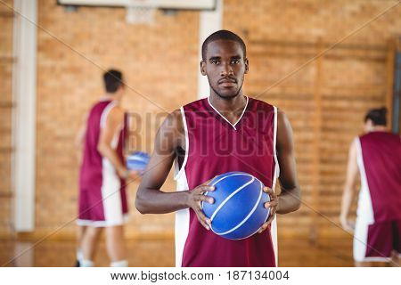 Portrait of confident basketball player holding a basketball in the court