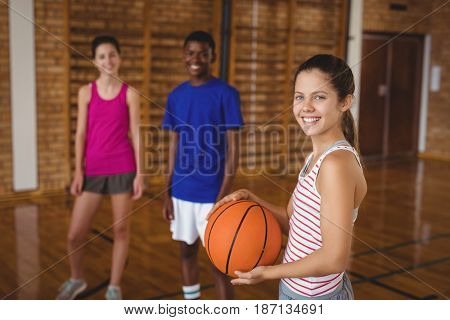 Portrait of smiling high school kids standing with basketball in the court