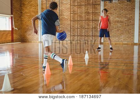 High school boys practicing football using cones for dribbling drill in the court