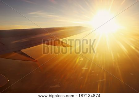 View of airplane wing and sun beams though the window.