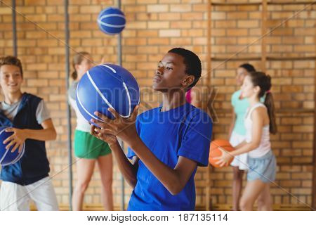 High school boy looking at basketball in the court