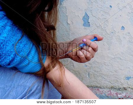 Young women use drugs in injection, young girl junkie with drug injection in palm, drugs addiction