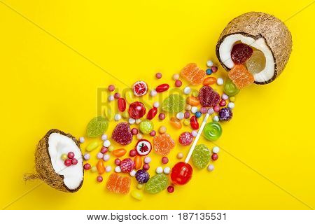 Colorful explosion of candies in coconut on yellow colored background creative still life flat lay style copy space