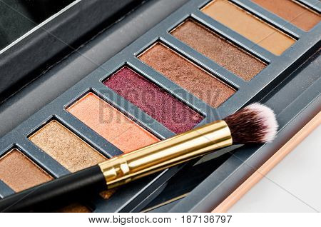 eyeshadow makeup in set palette with brush on white background.