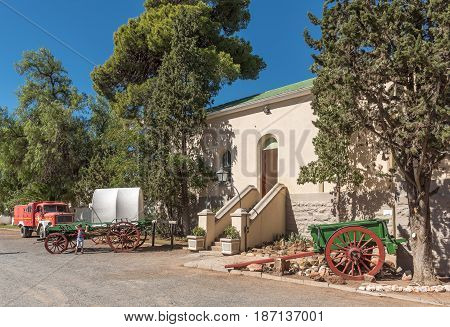 MATJIESFONTEIN SOUTH AFRICA - APRIL 2 2017: A street scene with historic fire truck oxwagon and horse drawn cart in front of the historic station building in Matjiesfontein