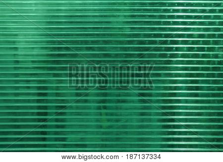 Green polycarbonate surface with objects behind. Industrial background, regular structure with horizontal structure. Plastic texture with place for text.