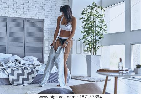 Getting dressed. Full length of beautiful young woman getting dressed while standing in the bedroom at home