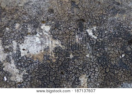 Old rubber texture, looks like a cracked ground. Black and gray wallpaper with dust and cracks, post-nuclear theme. Aged dirty surface.