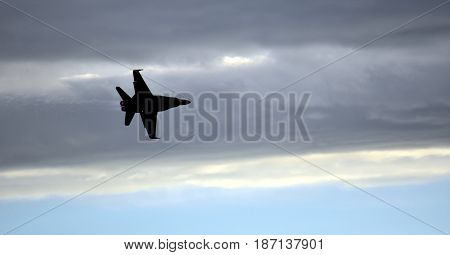 Albion Park, Australia - May 6, 2017. Silhouette of F18 Hornet fighter aircraft in flight. Clouds in the background. Wings Over Illawarra is an annual air show held at Illawarra Regional Airport.