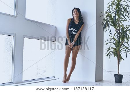 Confident in her beauty. Full length of beautiful young woman keeping hands clasped while standing near the window