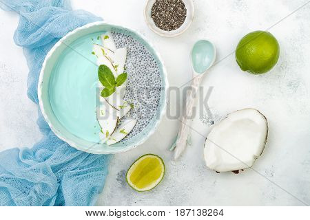Vegan blue spirulina smoothie and chia pudding bowl topped with coconut flakes and lime zest. Overhead flat lay top view