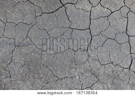 Gray cracked ground texture. Dry soil surface with lot of cracks. Natural desert background, post nuclear theme.