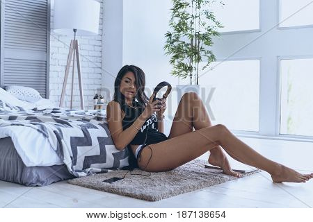 Tastefully tempting. Attractive young woman holding headphones and looking away while sitting on the floor at home